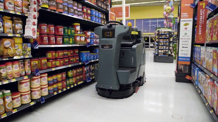 A riding floor scrubber without a driver navigating an aisle at Walmart.