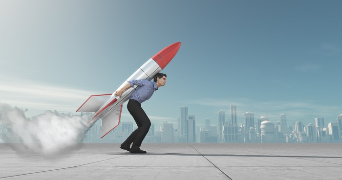 Businessperson on a rooftop with a big rocket strapped to his back.