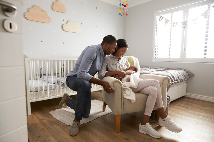 Two people with one sitting and holding a baby in a room with a crib.