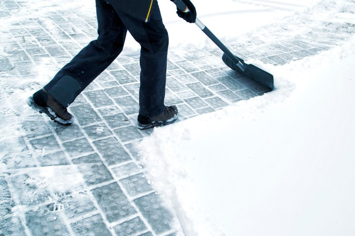 A person shovels a sidewalk.