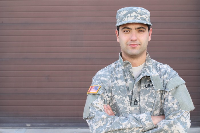 Man in fatigues with arms crossed