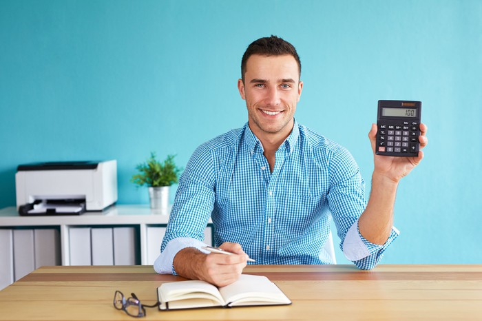 Man holding up calculator and smiling