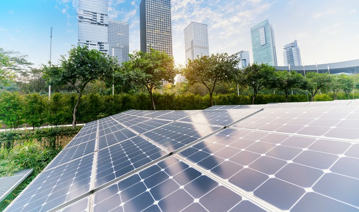 Solar panels with trees and skyscrapers in the background
