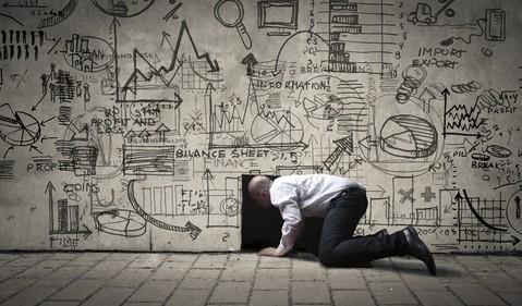 Man on knees in front of wall full of business diagrams
