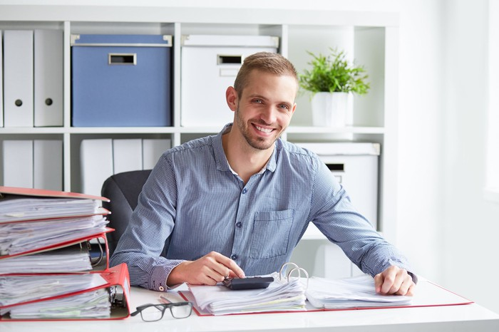 Smiling man typing on calculator