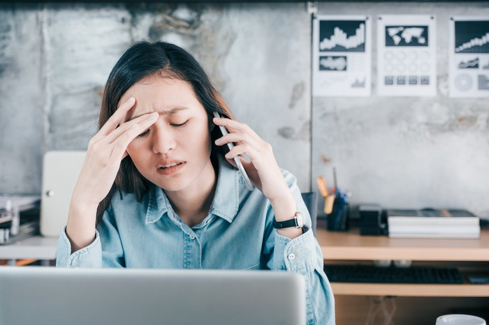 Woman with stressed expression holding her head while talking on phone, with a laptop in front of her