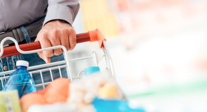 A hand pushing a shopping cart.