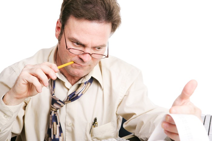 A man with a loosened tie chews on a pencil as he looks at a ticker tape in his hand.