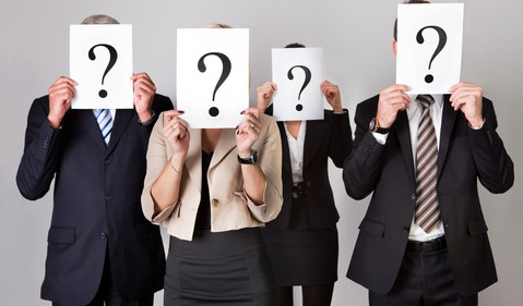 4 business people holding question mark signs