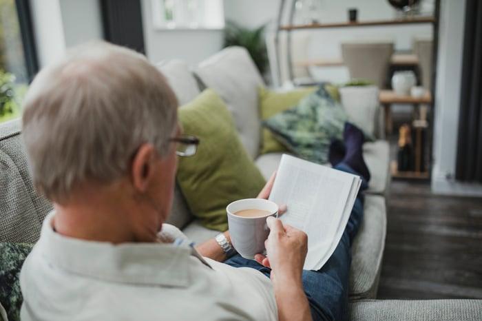 Older man reading magazine and holding mug