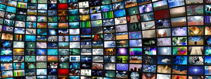 A wall of different TV screens as if in a TV studio.