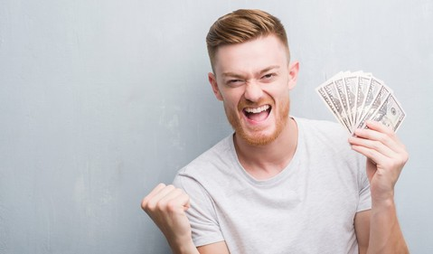 man smiling and holding cash_GettyImages-1042553490