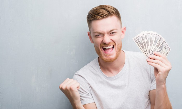 Man against gray background smiling and holding a bunch of 50-dollar bills