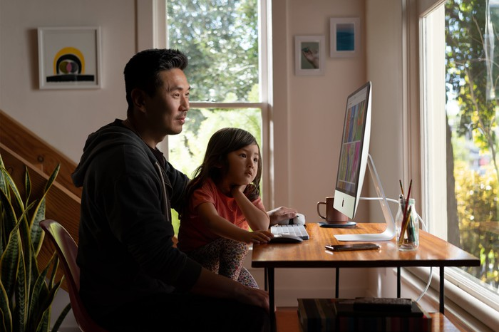 Man and daughter using an iMac