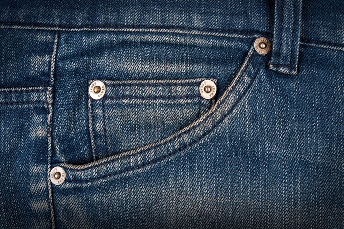 Close up of hip pocket on a pair of weathered blue jeans.