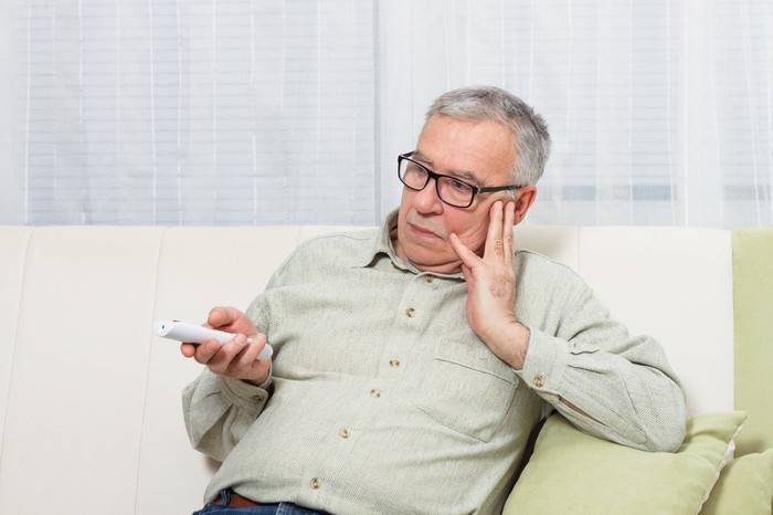 Older man with bored expression on couch with TV remote in hand