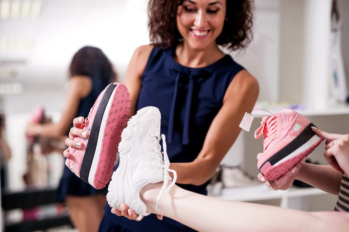 Two women try on sneakers at a shoe store.