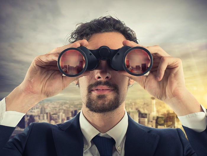 Man in suit looking through binoculars with a cityscape in the background