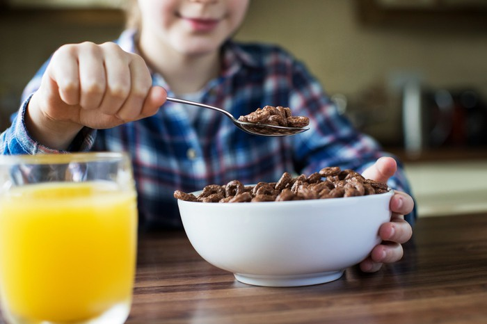 A young girl holding up a spoonful of breakfast cereal at a kitchen table, with a glass of orange juice in front of her.