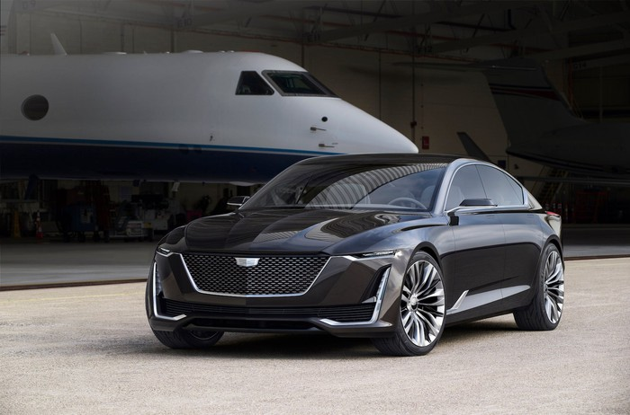 "The Cadillac Escala show car, a big, sleek luxury sedan with a distinctive coupe-like ""fastback"" roofline, is shown parked in an aircraft hangar. A private jet is visible in the background."