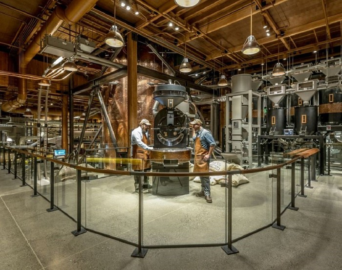 Inside of a coffee roastery, with two people working at a large piece of equipment.