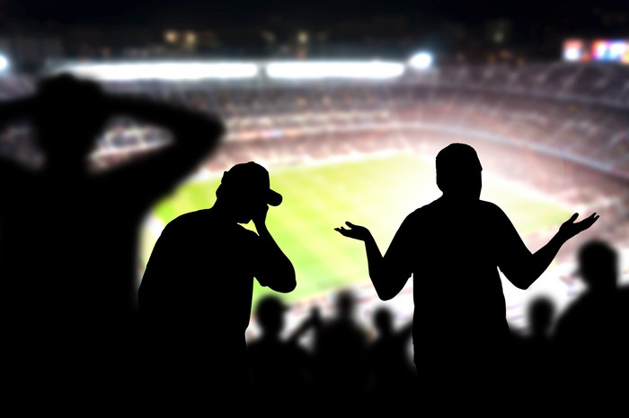 Silhouettes of fans making upset gestures in a sports stadium.
