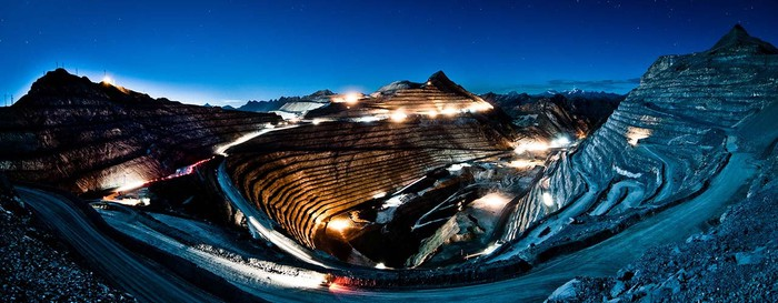 Open pit mine at night, with lights on and mountains surrounding.