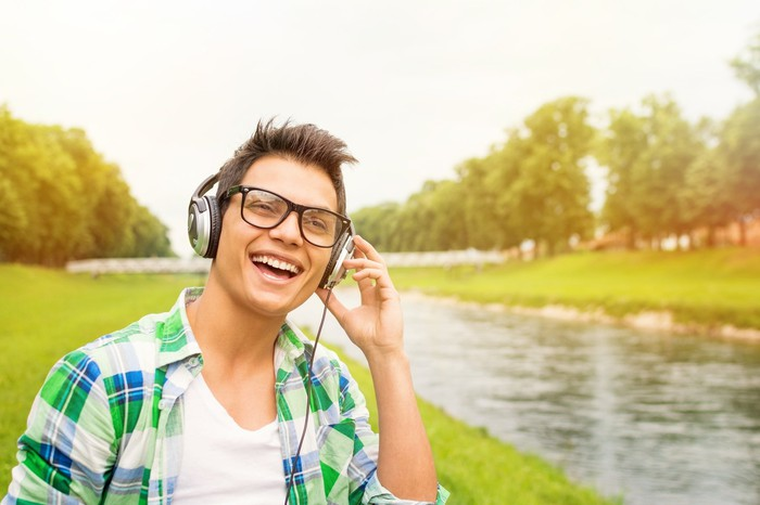 Young male adult outdoors walking in the green grass next to a stream with headphones and a big smile.