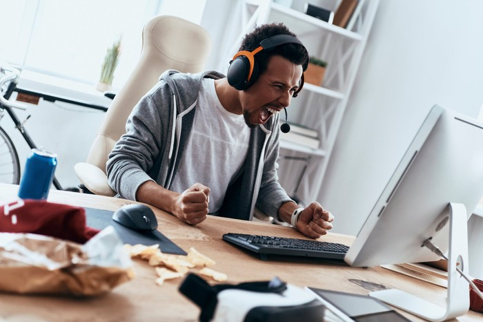 A man yelling into a headset looking at a computer.