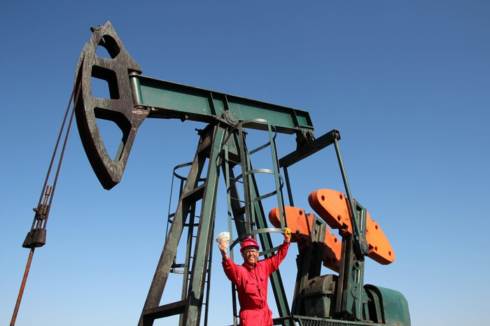 Oil worker holding cash in front of an oil pump.
