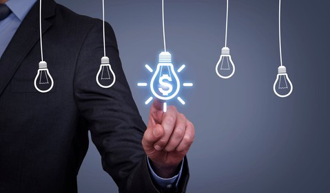 Businessman pointing to light bulb with dollar sign