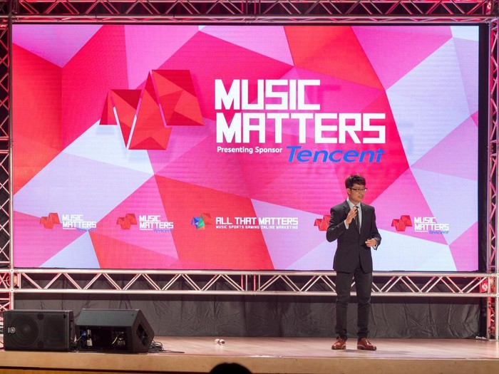 Person on stage with backdrop saying Music Matters with pink and white stripes.