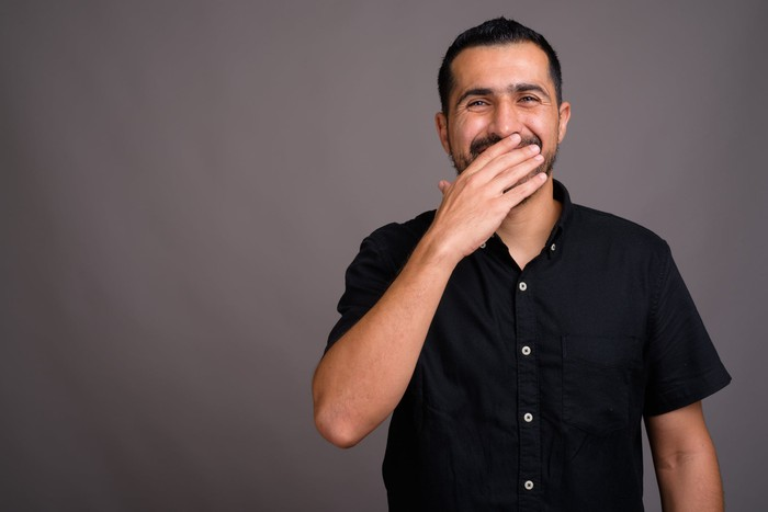 Laughing man with hand over his mouth