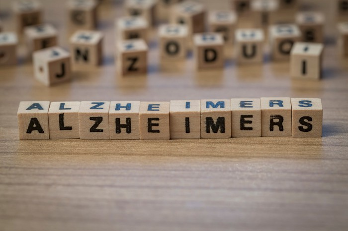"""Alzheimers"" spelled in wooden blocks with more wooden blocks with letters on them in the background."
