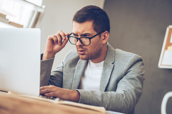 Man in grey jacket and white tee shirt at computer adjusting his glasses.