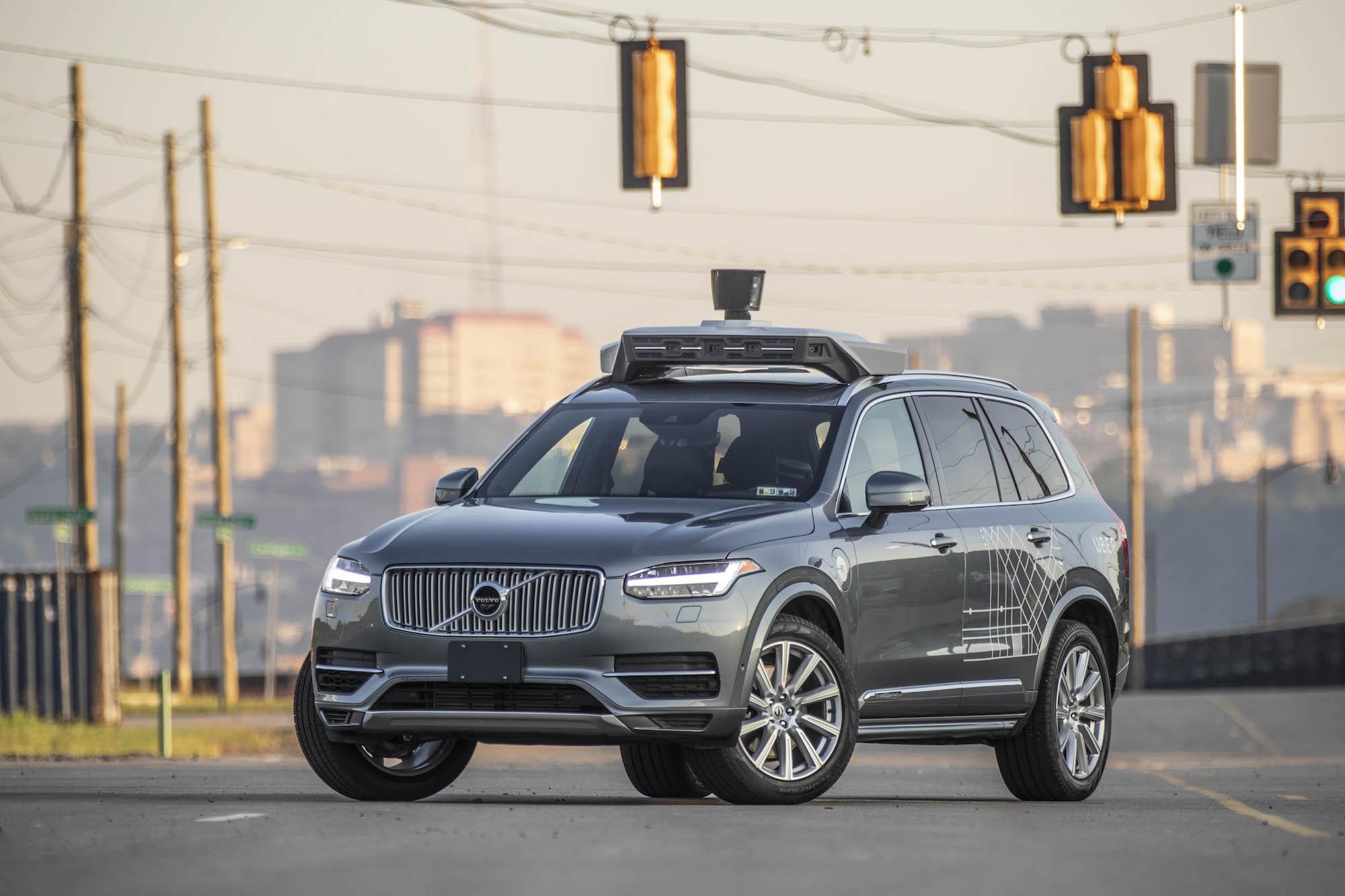 An autonomous SUV with Uber branding.