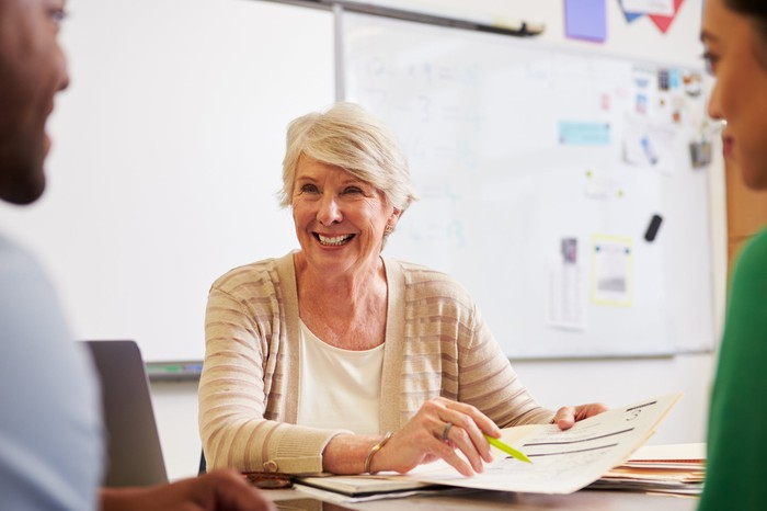 Older woman teaching teaching two students who are facing her.
