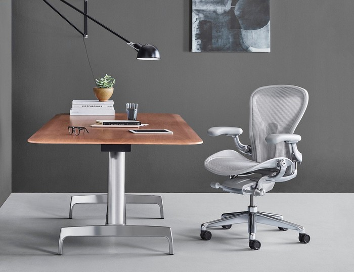 Grey ergonomic chair beside modern wood and steel desk.