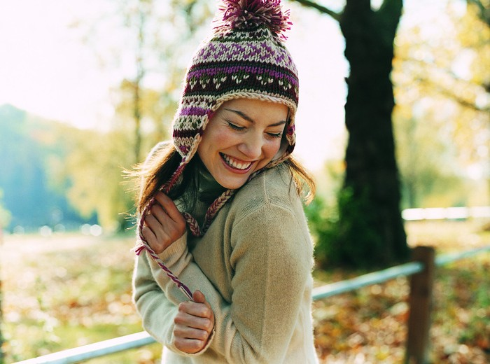 Young woman in bobble hat and sweater smiling in a fall landscape.