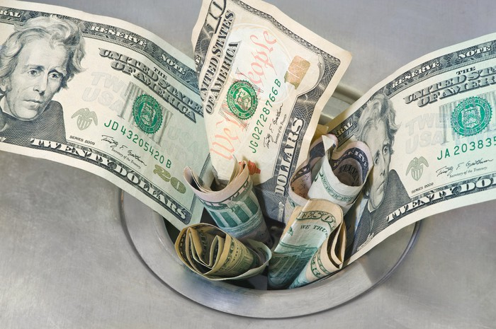A sink drain is shown, stuffed full of cash as if the money is going down the drain.
