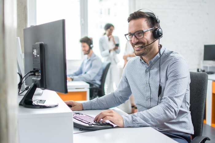 Smiling man with headset at computer