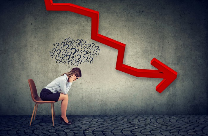 Depressed-looking businesswoman sitting on a chair with a downward pointing red arrow in the background.