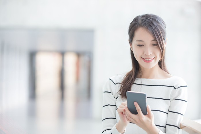 A young woman uses a smartphone.