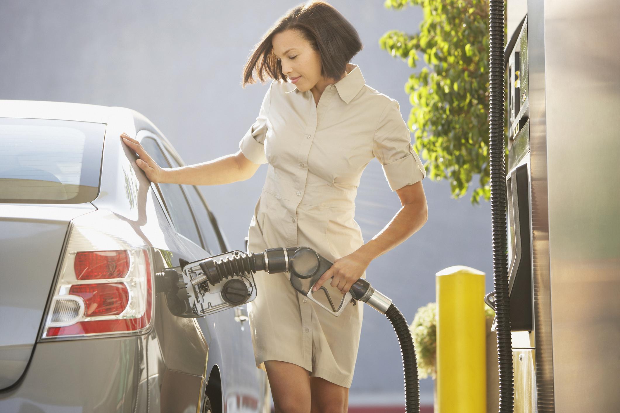 A woman pumping gas into a passenger car