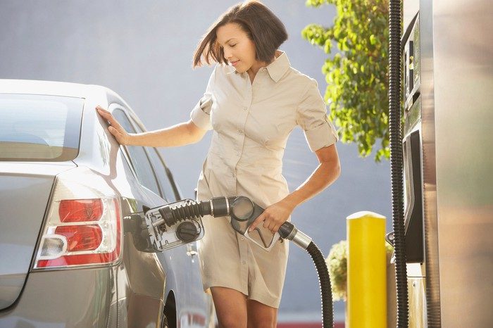 A woman pumping gas into a passenger car