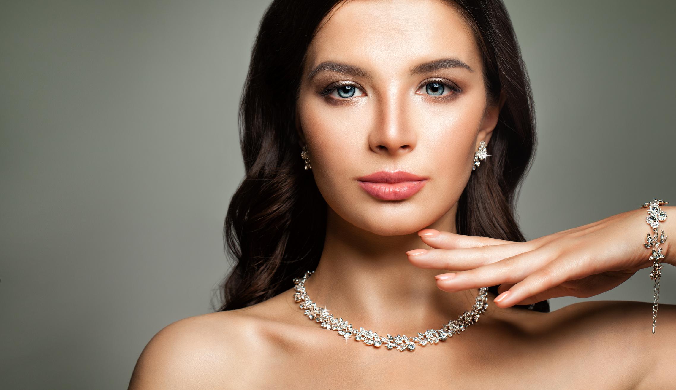 A woman wearing diamond earrings, necklace, and bracelet.