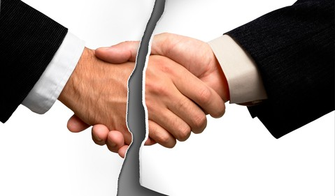 A picture of two people shaking hands that's torn in half.