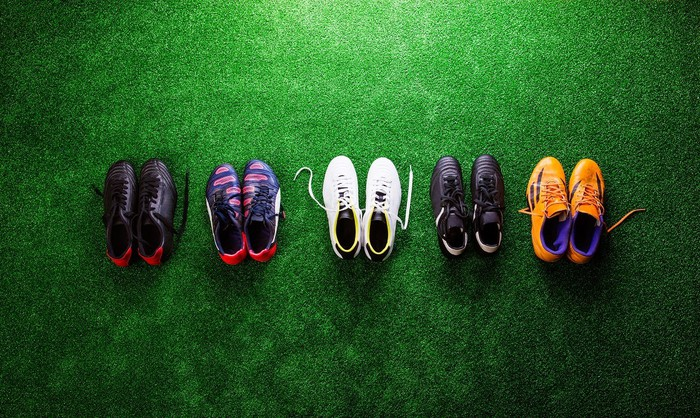 Soccer cleats lined up on a field.