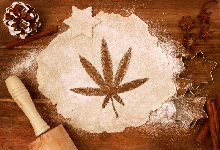 An image of a marijuana leaf cut into rolled-out dough on a baker's table.