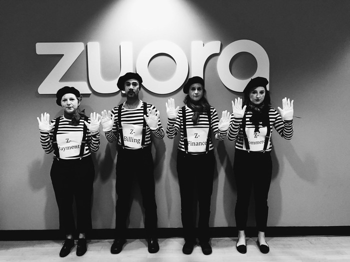 Four mimes standing in front of the Zuora logo.